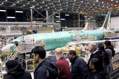 Посетители в сборочном цехе Boeing в Рентоне, штат Вашингтон, 7 декабря 2015 года. Авиационный рынок неплохо себя чувствует, несмотря на проблемы мировой экономики, а покупатели находят средства для покупок и получают заказанные самолеты, сообщили представители Boeing и Airbus на авиасалоне в Сингапуре. REUTERS/Matt Mills McKnight