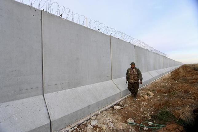 A Kurdish People's Protection Units (YPG) fighter walks near a wall, which activists said was put up by Turkish authorities, on the Syria-Turkish border in the western countryside of Ras al-Ain, Syria January 29, 2016. REUTERS/Rodi Said