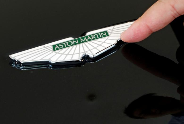 Sales Manager Raymond Liu points to an Aston Martin insignia on a car as he explains how each is handmade, at their showroom in Singapore August 1, 2014.     REUTERS/Edgar Su