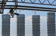 Рабочий на месте строительства парка развлечений в Хэфэе в китайской  провинция Аньхой. Китайские законодатели вернулись к работе после празднования Нового года по лунному календарю, пообещав обеспокоенным местным и зарубежным инвесторам, что Пекин поддержит рост экономики, сохранит устойчивость валюты и стабильность рынка труда, даже в то время, когда разросшиеся отрасли промышленности находятся на стадии реструктуризации.      REUTERS/Stringer