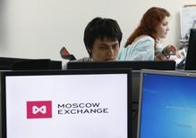 Трейдеры работают на Московской фондовой бирже.  Российские фондовые индексы завершают торги среды на сессионных максимумах благодаря росту нефтяных цен, который был спровоцирован вечером заявлениями министра нефти Ирана о готовности поддержать любые попытки стабилизации рынка. REUTERS/Sergei Karpukhin