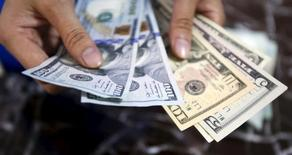 Funcionário segura notas de dólar em banco, em Hanói, Vietnã. 12 de agosto de 2015.  REUTERS/Kham