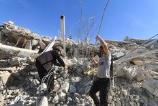 """Люди ищут выживших в руинах разрушенной бомбардировкой больницы в провинции Идлиб.  Благотворительная организация """"Врачи без границ"""" призвала провести независимое расследование авиаударов по сирийской больнице, в результате которого погибли 25 человек, заявив, что удары могли быть выполнены силами проправительственной коалиции. REUTERS/Ammar Abdullah"""