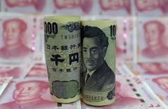 Банкноты в 1000 иен на фоне китайских юаней. Иена выросла в пятницу, достигнув нового пика двух с половиной лет к евро, отчасти благодаря возобновившемуся спросу на безопасную японскую валюту, так как цены на нефть и акции снова пошатнулись. REUTERS/Jason Lee