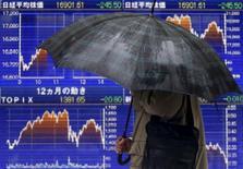 Un peatón con un paraguas pasea frente a una pantalla electrónica que muestra las fluctuaciones de índice japonés Nikkei en Tokio, el 18 de enero de 2016. Las acciones japonesas cayeron el viernes en un débil volumen de negocios luego de que un yen más fuerte y un declive de los precios del petróleo minaron el apetito por el riesgo. REUTERS/Yuya Shino