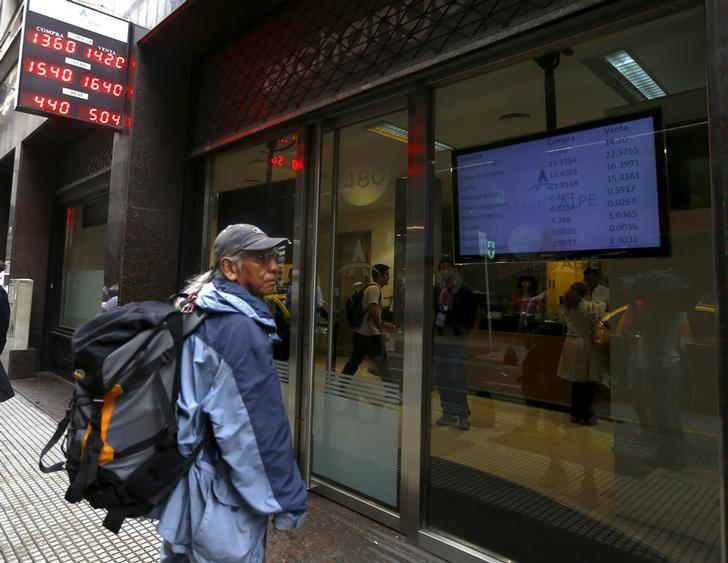 A pedestrian looks at currency exchange rates board at a money exchange in Buenos Aires' financial district, Argentina, December 17, 2015.  REUTERS/Enrique Marcarian