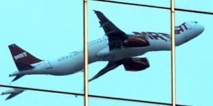 Самолет отражается в окнах здания во время вылета из аэропорта в Сан-Паулу 7 декабря 2006 года. Количество бронирований авиабилетов в страны Латинской Америки и Карибского бассейна снизилось после того, как американское ведомство посоветовало беременным женщинам отказаться от поездок в районы распространения вируса Зика, сообщила в пятницу аналитическая компания ForwardKeys. REUTERS/Paulo Whitaker