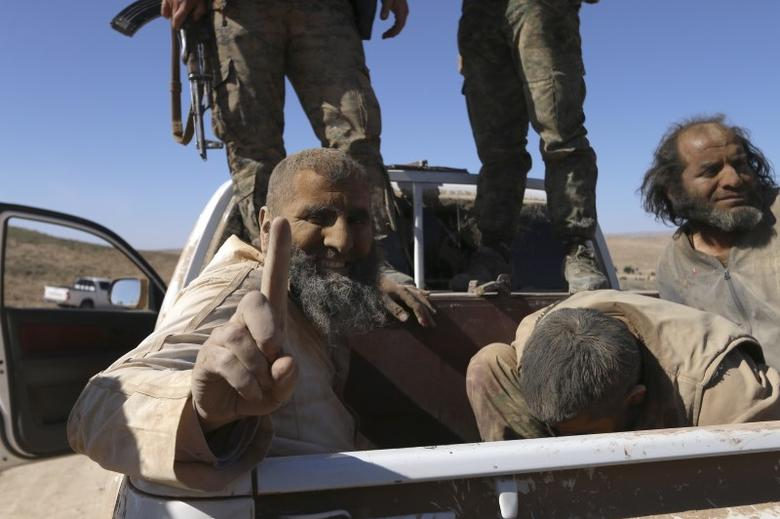 An Islamic State fighter gestures while being held prisoner with fellow fighters under Democratic Forces of Syria fighters as they ride a pick-up truck near al-Shadadi town, Hasaka countryside, Syria, February 18, 2016. REUTERS/Rodi Said