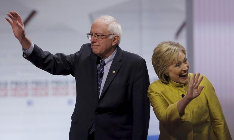 Bernie Sanders and Hillary Clinton wave as they arrive on stage before of the start of the PBS NewsHour Democratic presidential candidates debate in Milwaukee, Wisconsin, February 11, 2016.  REUTERS/Jim Young