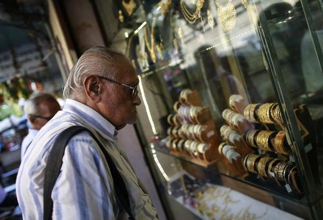 A man looks at gold bangles displayed at a jewellery showroom at a market in Mumbai October 21, 2014. REUTERS/Danish Siddiqui/Files