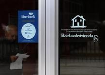 Liberbank dijo el miércoles que su beneficio neto atribuido se elevó un 9,9 por ciento en 2015 hasta alcanzar los 129 millones de euros, apoyándose en un aumento del 5 por ciento en el margen de intereses a 494 millones. En la imagen, un hombre lee unos papeles en la sede de Cajastur, parte de Liberbank, en Oviedo, el 22 de mayo de 2014. REUTERS/Eloy Alonso