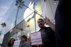 Участники немногочисленной уличной акции в поддержку отказа Apple от взлома мобильного телефона по требованию ФБР. Санта-Моника, Калифорния, США, 23 февраля 2016 года. Почти половина американцев поддерживают решение Apple Inc противостоять постановлению федерального суда, потребовавшего взломать блокировку смартфона, использованного стрелком из Сан-Бернардино Ризваном Фаруком, свидетельствуют данные общенационального онлайн-опроса, проведенного Рейтер и Ipsos. REUTERS/Lucy Nicholson