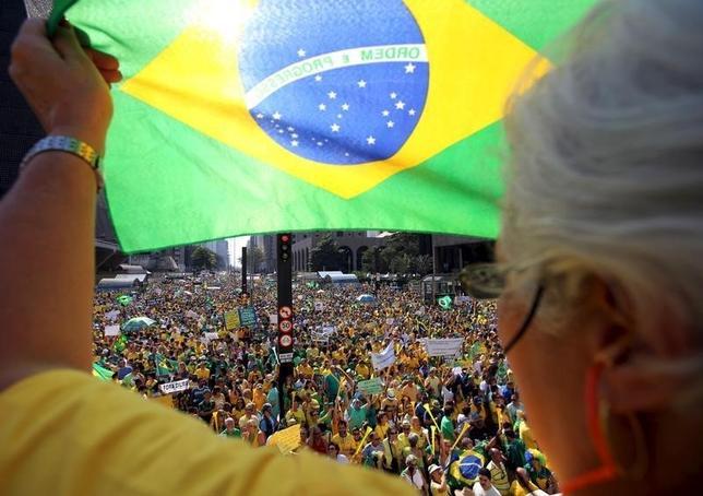 2月24日、格付け会社ムーディーズはブラジルの格付けをジャンク級となる「Ba2」に2段階引き下げた。写真は反政府デモで国旗を掲げる参加者。昨年8月撮影。(2016年 ロイター/Paulo Whitaker)