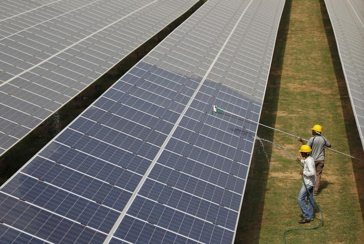 Workers clean photovoltaic panels inside a solar power plant in Gujarat, India, July 2, 2015. REUTERS/Amit Dave