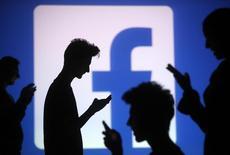 """Люди позируют с мобильными телефонами на фоне экрана с изображением логотипа. Фотоиллюстрация сделана в Зенице, Босния и Герцеговина, 29 октября 2014 года. Социальная сеть Facebook сообщила в среду, что расширенная версия кнопки """"Like"""" (""""Нравится"""") под названием """"Reactions"""" (""""Реакции"""") теперь станет доступна пользователям по всему миру. REUTERS/Dado Ruvic"""