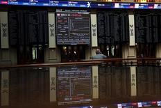 El Ibex-35 cerró el miércoles con una caída superior al tres por ciento, con prácticamente todos sus valores en rojo, debido a la preocupación por la nueva caída de precio del crudo y la rebaja de Moody's al rating de Brasil, un mercado al que están expuestas empresas españolas como Santander o Telefónica. En la imagen de archivo, un operador habla por teléfoon mientras observa unas pantallas de ordenador en la bolsa de Madrid, el 29 de junio de 2015 REUTERS/Susana Vera