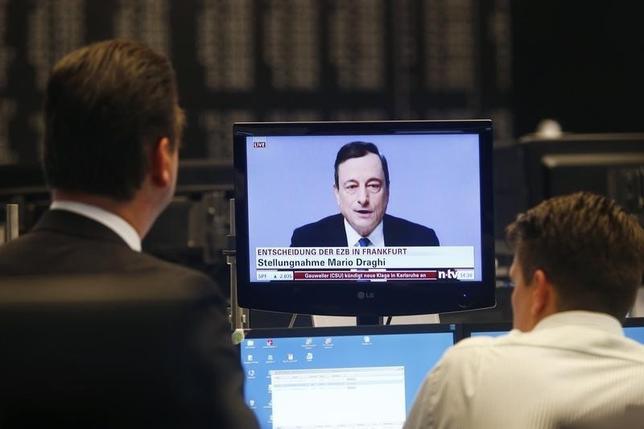 2月24日、スイスのピクテによると、過去最大となる45%の独国債がECBの買い入れ対象から外れた。写真はドラギ総裁の会見を見る独市場関係者。昨年1月撮影。(2016年 ロイター/Ralph Orlowski)