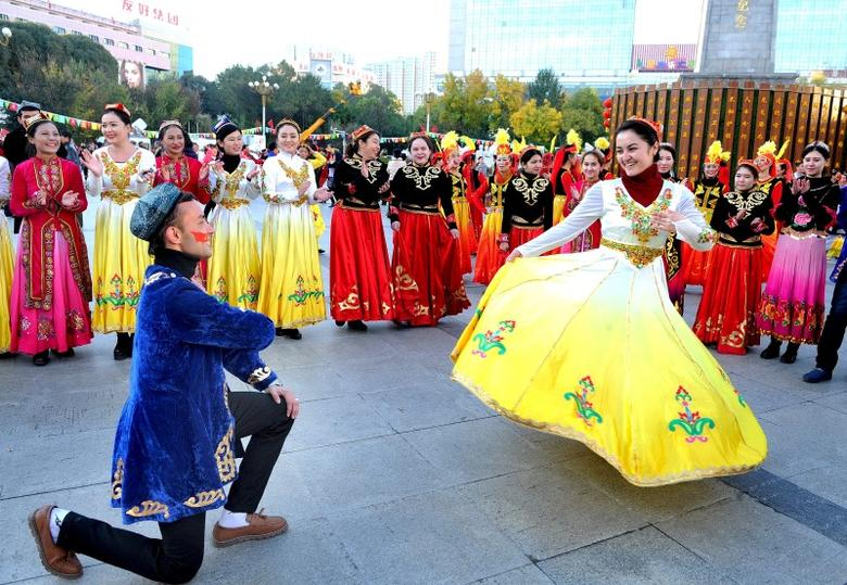 People wearing costumes perform at a square during a celebration on the 60th anniversary of the founding of the Xinjiang Uighur Autonomous Region, in Urumqi, Xinjiang Uighur Autonomous Region, October 1, 2015. REUTERS/Stringer