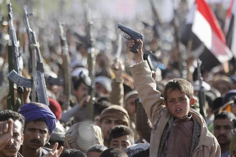 A boy shouts slogans as he raises a gun during a rally against U.S. support to Saudi-led air strikes, in Yemen's capital Sanaa, February 19, 2016. REUTERS/Mohamed al-Sayaghi