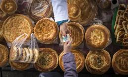 Покупатель передает деньги продавцу лепешек на Зеленом базаре в Алма-Ате 23 января 2015 года. McDonald's Corp в партнёрстве с родственником президента Казахстана назначил на март открытие первого ресторана всемирно известной сети фастфуда - проект, в который владелец франшизы вложил $3,5 миллиона. REUTERS/Shamil Zhumatov