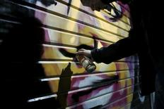 Artist Solomon Souza,22, spray-paints a portrait on the metal shutter of a closed storefront in Mahane Yehuda, one of Jerusalem's most popular outdoor markets February 24, 2016. REUTERS/Ronen Zvulun