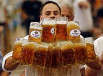 """Немец Оливер Стремпфл пытается установить мировой рекорд, перенося пивные кружки в Абенсберге 7 сентября 2014 года. Немецкая группа, занимающаяся проблемами окружающей среды, сообщила в четверг об обнаружении в 14 наиболее популярных сортах немецкого пива следов широко используемого гербицида глифосата, что рискует нанести удар по репутации страны как производителя """"чистого"""" пива. REUTERS/Michael Dalder"""