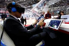 An employee sits inside a virtual reality connected car cockpit built by Segula Technologies during the first press day ahead of the 85th International Motor Show in Geneva March 3, 2015. REUTERS/Arnd Wiegmann