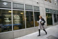 El grupo bancario Kutxabank dijo el sábado que aumentó un 45 por ciento su beneficio atribuible el pasado año hasta los 219  millones de euros, gracias a un contexto de recuperación económica, aunque todavía penalizado por unos bajos tipos de interés. En la imagen de archivo, una mujer pasea frente a una sucursal de Kutxabank en Madrid, el 30 de octubre de 2008. REUTERS/Andrea Comas