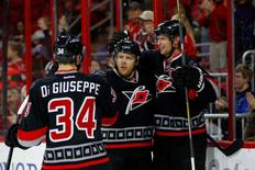 Jan 24, 2016; Raleigh, NC, USA; Carolina Hurricanes forward Kris Versteeg (32) is congratulated by  forward Eric Staal (12) and forward Phillip Di Giuseppe (34) after his second period goal against the Calgary Flames at PNC Arena. Mandatory Credit: James Guillory-USA TODAY Sports