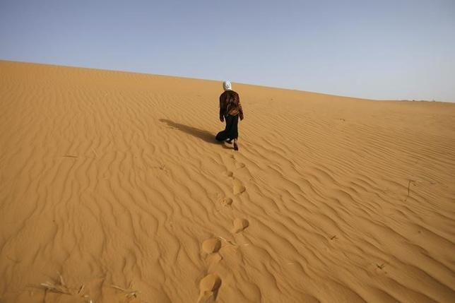 2月24日、複数の国際団体が地中海を横断して欧州に向かう途中で溺死した移民の数を調査しているが、サハラ砂漠での死者数は誰もカウントしていない。写真はサハラ砂漠のはずれにある、アルジェリアのティミムンで砂の上を歩く少女。2008年3月撮影(2016年 ロイター/Zohra Bensemra)
