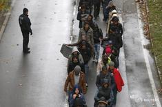 Мигранты идут по улице после пересечения австрийско-германской границы в Пассау, Германия 29 октября 2015 года. Канцлер Германии Ангела Меркель в воскресенье выступила в защиту своей политики открытых дверей по отношению к беженцам, отвергнув какие-либо ограничения численности прибывающих в страну мигрантов, несмотря на разногласия внутри её собственного правительства. REUTERS/Michaela Rehle