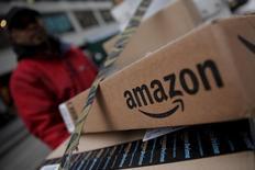 Un repartidor cerca de cajas de Amazon, en Nueva York, 29 de enero de 2016. El minorista online Amazon se dispone a entrar en el mercado británico de productos frescos tras alcanzar un acuerdo con el grupo de supermercados Morrisons, lo que potencialmente podría elevar aún más la competencia en el sector. REUTERS/Mike Segar