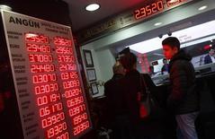 Unas personas en una casa de cambios en Estambul, dic 16, 2014. Los flujos hacia los bonos y acciones de mercados emergentes se mantuvieron mayormente estables en febrero tras siete meses consecutivos de fuertes salidas de dinero ya que el apetito por el riesgo mejoró levemente, según el Instituto Internacional de Finanzas (IFF).  REUTERS/Murad Sezer