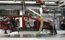 La actividad manufacturera española se expandió de nuevo en febrero y las fábricas contrataron más personal, haciendo caso omiso de más de dos meses de incertidumbre política postelectoral, según un sondeo difundido el martes. Imagen de un trabajador de una fábrica de SEAT, del grupo Volkswagen, trabajando en un motor de un SEAT Leon, en Martorell, cerca de Barcelona el 5 de diciembre de 2014. REUTERS/Gustau Nacarino