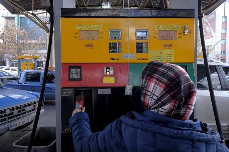 An Iranian woman puts a nozzle back after refuelling her car at a petrol station in Tehran, Iran, January 25, 2016. REUTERS/Raheb Homavandi/TIMA