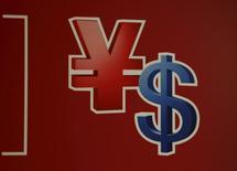 """Moody's Investors Service bajó el miércoles la perspectiva del rating de China a """"negativa"""" desde """"estable"""", citando la incertidumbre sobre la capacidad de las autoridades para implementar reformas, la creciente deuda del país y el descenso de sus reservas cambiarias. En la foto, los símbolos del yuan (i) y del dólar en un cajero automático en la torre del Banco de China en Hong Kong el 12 de noviembre de 2015.      REUTERS/Bobby Yip"""