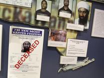 """Бумага с информацией о находящемся в розыске Усаме бен Ладене и надписью """"Скончался"""" в офисе ФБР в Вашингтоне. 26 ноября 2013 года. Лидер """"аль-Каиды"""" Усама бен Ладен в письмах и других документах обозначил, на что должны пойти минимум $29 миллионов его средств и ценностей после его смерти, попросив использовать их для продолжения глобального джихада. REUTERS/Larry Downing"""