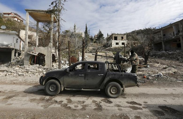Forces loyal to Syria's President Bashar al-Assad drive a vehicle mounted with an anti-aircraft weapon in the town of Rabiya after they recaptured the rebel-held town in coastal Latakia province, Syria January 27, 2016. REUTERS/Omar Sanadiki