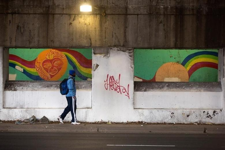 A man walks past concrete barriers installed under an overpass to deter homeless camping in Chicago, December 4, 2014.  REUTERS/Andrew Nelles