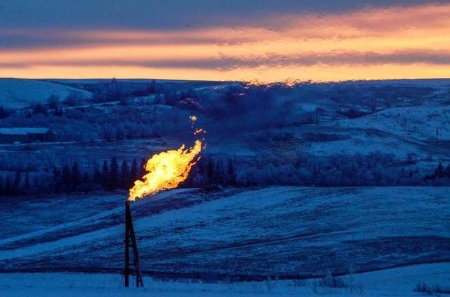 A natural gas flare on an oil well pad burns as the sun sets outside Watford City, North Dakota January 21, 2016. Persistent low oil prices have lead to slower business in much of North Dakota's Bakken oil fields.  The collapse of U.S. oil and gas investment could have further to fall and Americans are showing signs they spend less of their windfall from lower gasoline prices than in the past, darkening the outlook for the U.S. economy.   REUTERS/Andrew Cullen - RTX23LBT
