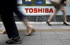 Peatones caminan junto al logo de Toshiba Corp, afuera de una tienda en Tokio. 14 de septiembre de 2015. Toshiba Corp está solicitando a tres prestamistas japoneses unos 1.800 millones de dólares en créditos adicionales para financiar su reestructuración tras un escándalo contable, dijeron el jueves fuentes con conocimiento directo del asunto. REUTERS/Toru Hanai