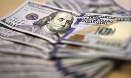 Долларовые купюры в Йоханнесбурге 13 августа 2014 года. Доллар перешел к обороне относительно основных валют в пятницу после того, как слабые данные о занятости в сфере услуг ухудшили ожидания повышения процентной ставки Федрезервом США в ближайшее время, рынок ждет официального отчета о занятости, который будет опубликован позднее в пятницу. REUTERS/Siphiwe Sibeko