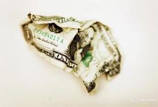 Мятая долларовая купюра в Торонто 22 октября 2008 года.  Крупнейший производитель труб в России ТМК в четвертом квартале 2015 года получил $371 миллион чистого убытка из-за обесценения своих американских активов, но не собирается избавляться от бизнеса в США и будет его поддерживать. REUTERS/Mark Blinch