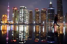 Женщина в финансовом районе Шанхая 5 марта 2015 года. Масштабные покупки недвижимости в Шанхае могут говорить о формирования нового пузыря на рынке, всего несколько месяцев спустя после обвала китайских акций, и это грозит экономике проблемами, подобными тем, что давят на неё с 2012 года. REUTERS/Aly Song