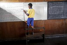 A student stands on a bench to write on the board at a floating school in the Makoko fishing community on the Lagos  Lagoon, Nigeria February 29, 2016. REUTERS/Akintunde Akinleye