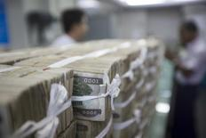 Stacks of Myanmar kyat are seen on the counter before a client collects them, at a bank in Yangon, Myanmar October 19, 2015. REUTERS/Minzayar