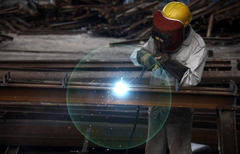 A worker welds at a machinery manufacturing factory in Huaibei, Anhui province in this August 20, 2013 file photo. REUTERS/Stringer