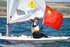 China's Xu Lijia holds her national flag as she celebrates winning the women's Laser Radial class sailing competition at the London 2012 Olympic Games in Weymouth and Portland, southern England, August 6, 2012.   REUTERS/Benoit Tessier