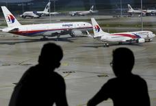 Men watch Malaysia Airlines aircraft at Kuala Lumpur International Airport in Sepang, Malaysia, in this picture taken March 2, 2016.  REUTERS/Olivia Harris