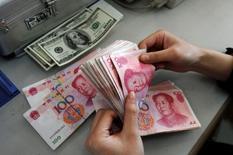 Un empleado cuenta billetes de yuan en una sucursal del Banco de China, en Changzhi, China. 9 de marzo de 2010. Las reservas de China en moneda extranjera, las más grandes del mundo, cayeron en febrero en 28.570 millones de dólares, a 3,20 billones de dólares, su nivel más bajo desde diciembre del 2011, mostraron el lunes datos del banco central. REUTERS/Stringer